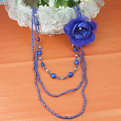 drie lagen lange ketting van blauwe Seed Pearl + Acryl + corsage